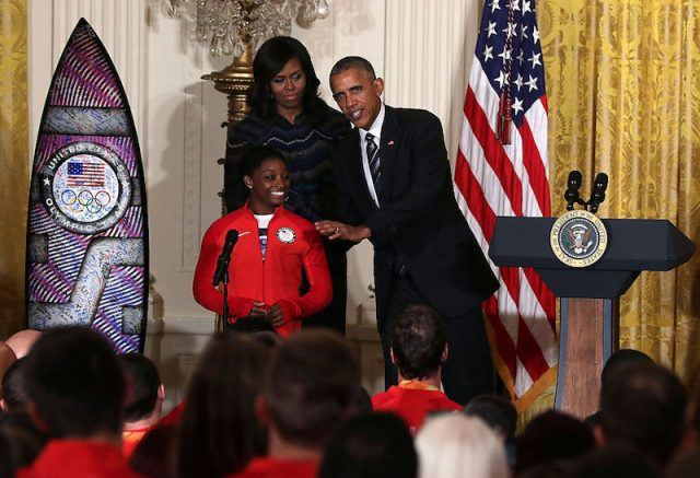 Former President Obama, Michelle Obama and Simone Biles on stage.