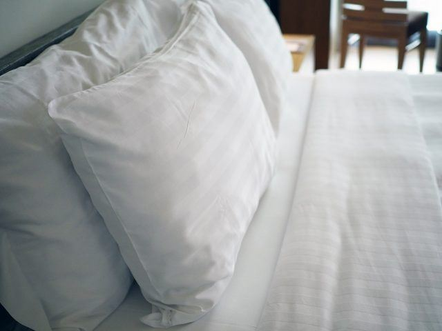 Big white soft pillows on a white luxury cozy bed