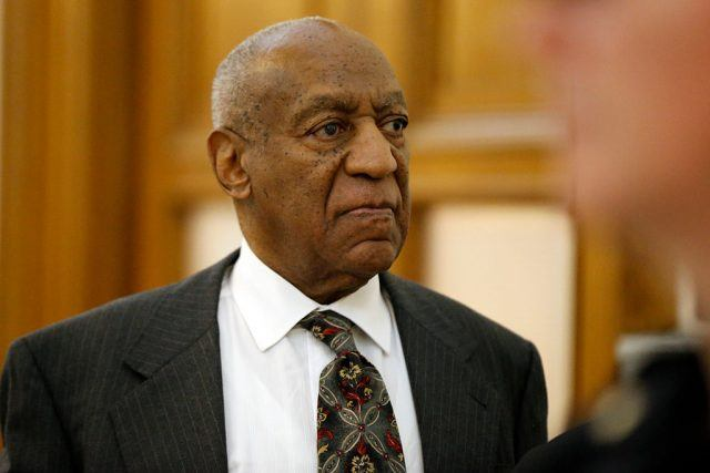 Bill Cosby staring straight ahead while wearing a suit and tie.
