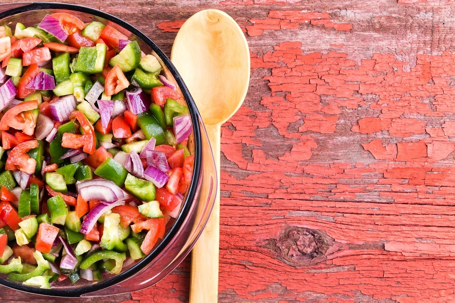 A large salad of veggies next to a wooden spoon