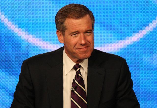 Brian Williams smiling as he sits behind a desk.