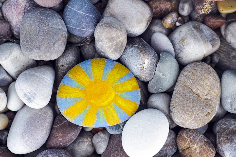 Bright sun painted on pebble with stones background