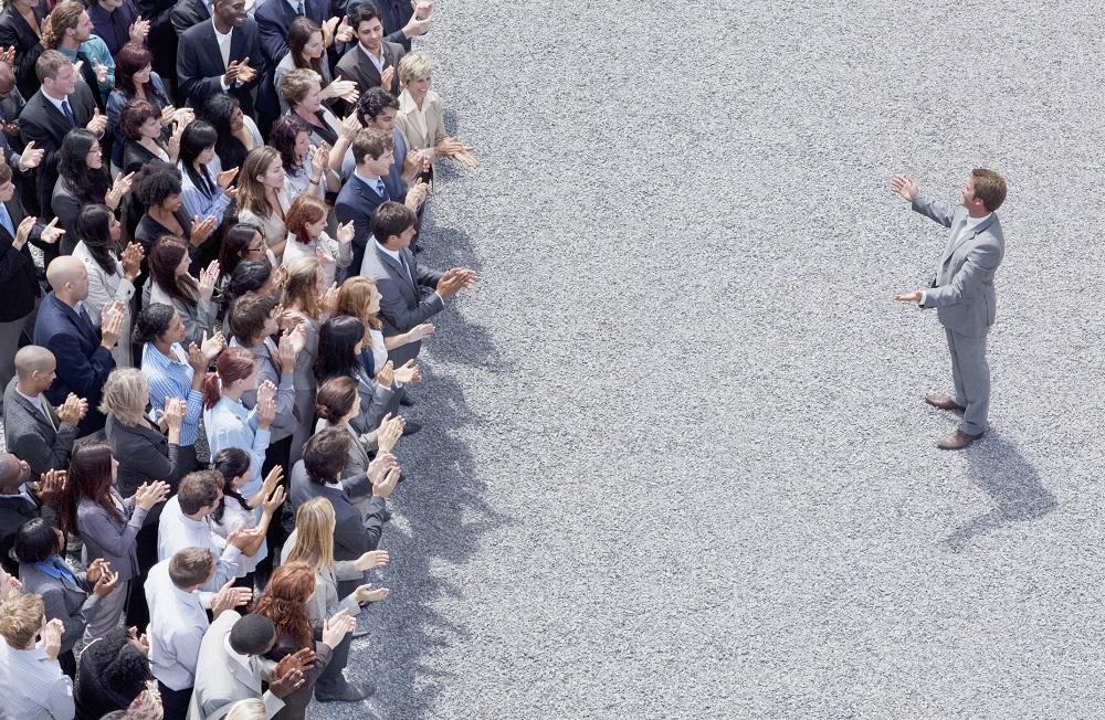 Businessman addressing clapping crowd