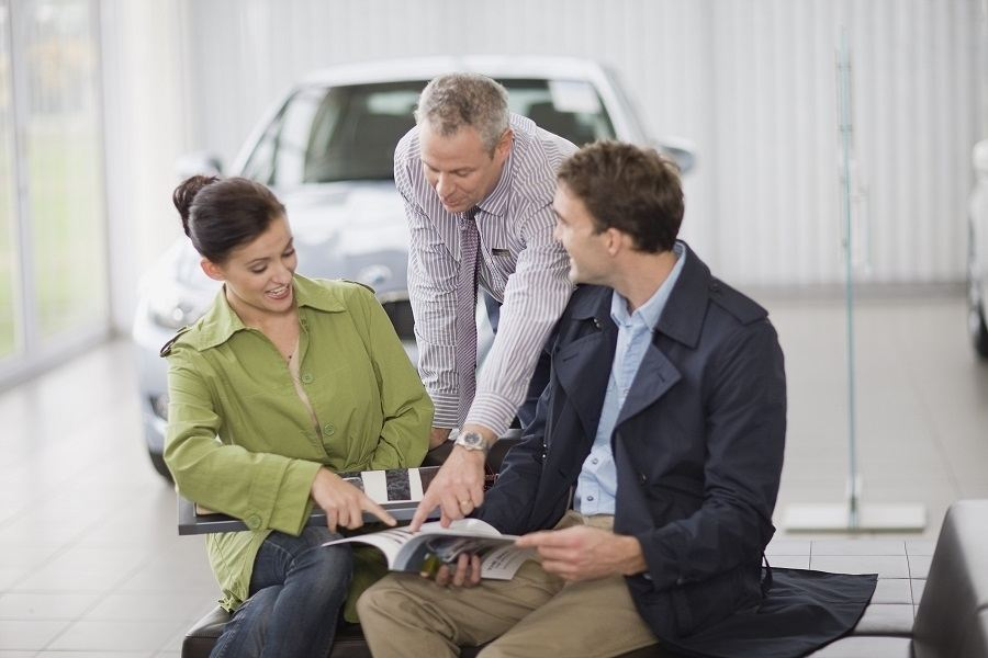 salesman talking with couple to sell a car