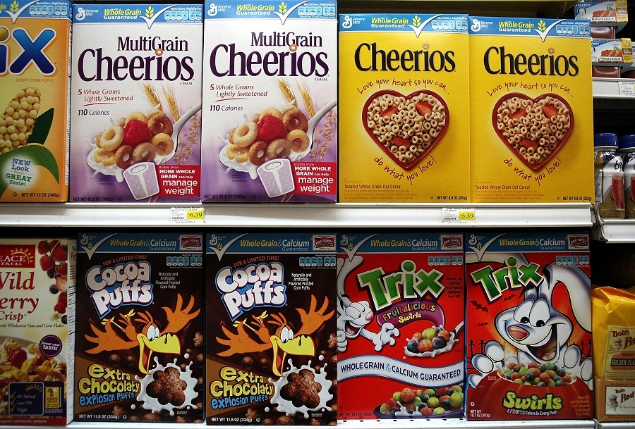 Breakfast cereals lined up on a shelf.