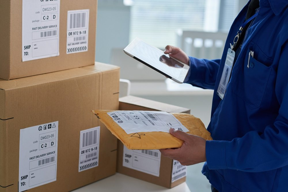 mail worker checking information on parcels
