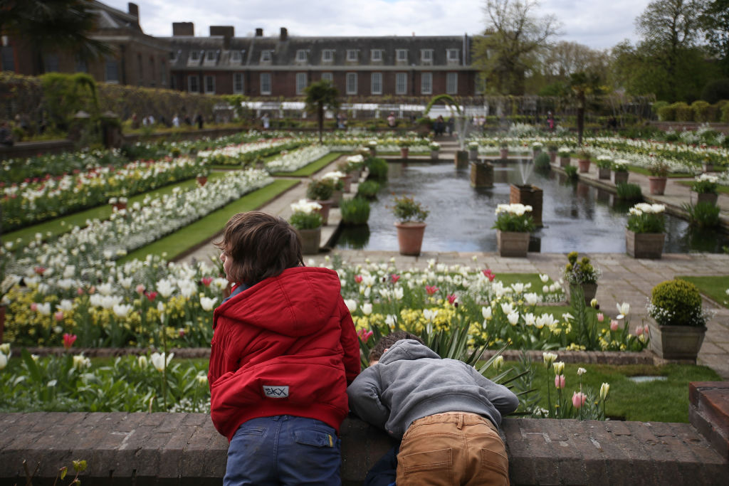 Children lean over the wall outside the White Garden, created to celebrate the life of Diana