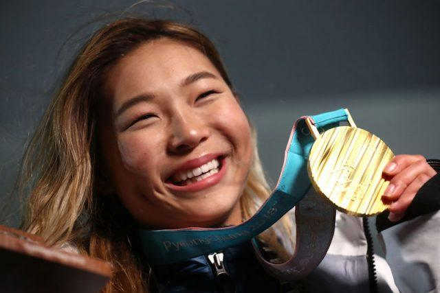 Chloe Kim smiling and holding up her gold medal.