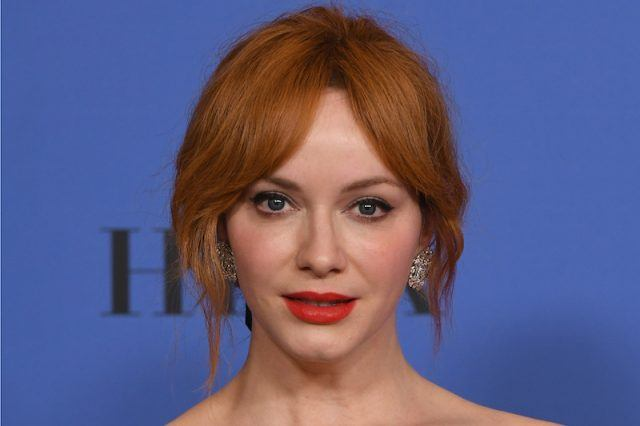 Christina Hendricks wearing red lipstick and jeweled earrings on a red carpet.