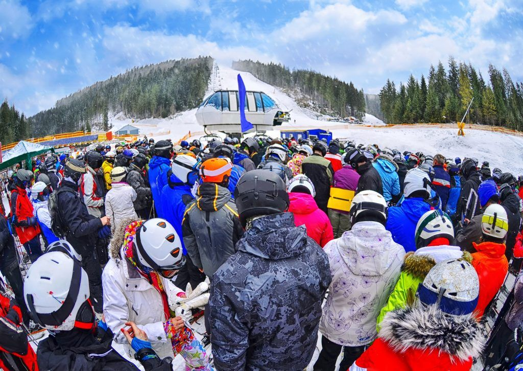 People stand before a ski lift in line in Bukovel