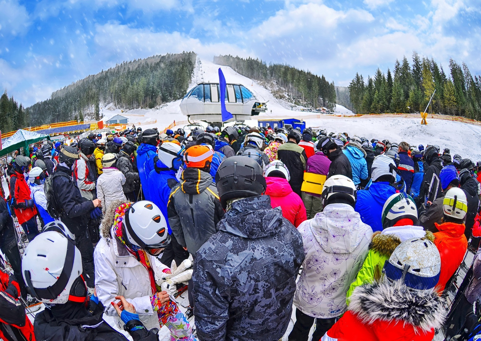 People stand before ski lift in queue in Bukovel