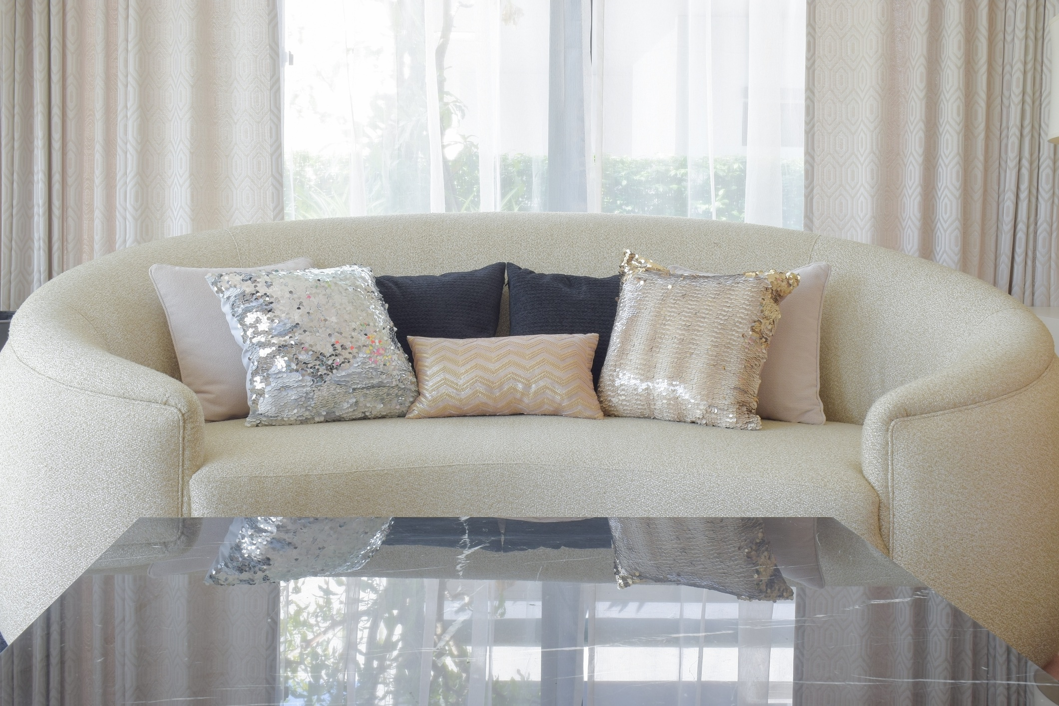 Round shape sofa with luxury style pillows and marble top table in foreground