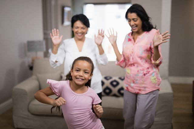 A family cheering as a small girl dances in a living room.