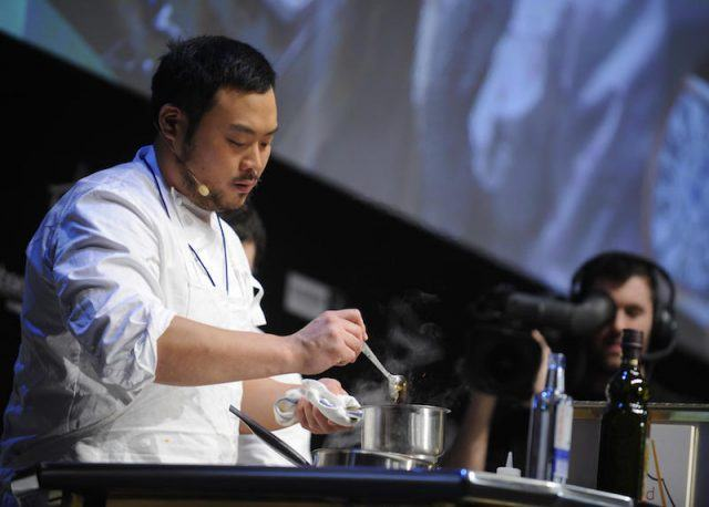 David Chang stirring the ingredients in a small silver pot.