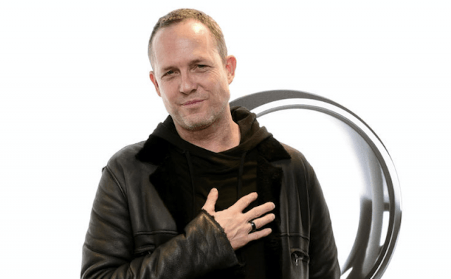 Dean Winters posing with his hand on his chest.