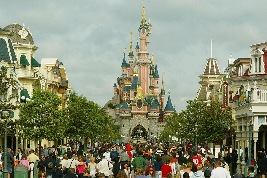 A crowd of tourists walk toward the Sleeping Beauty castle