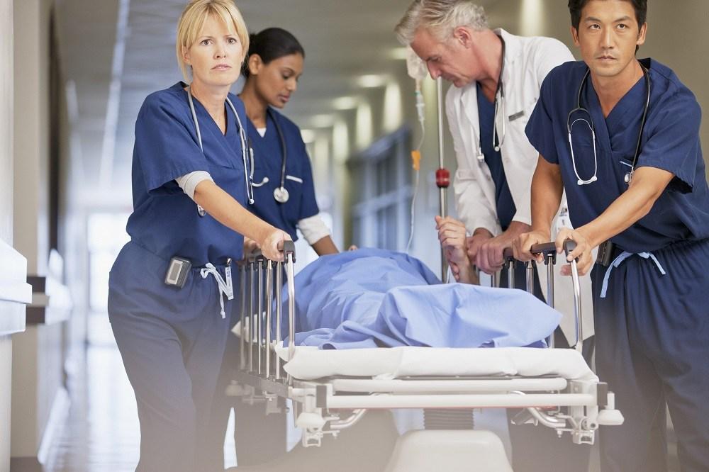 Doctor and nurses wheeling patient