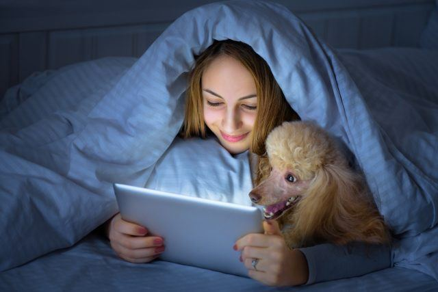 Girl with her dog on the bed with tablet.