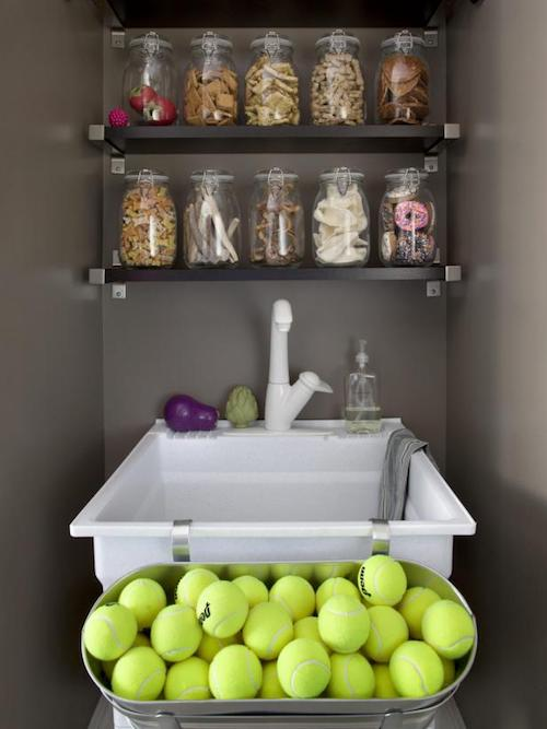 A silver container of golf balls, a white sink and a cabinet of dog treats on a wall.