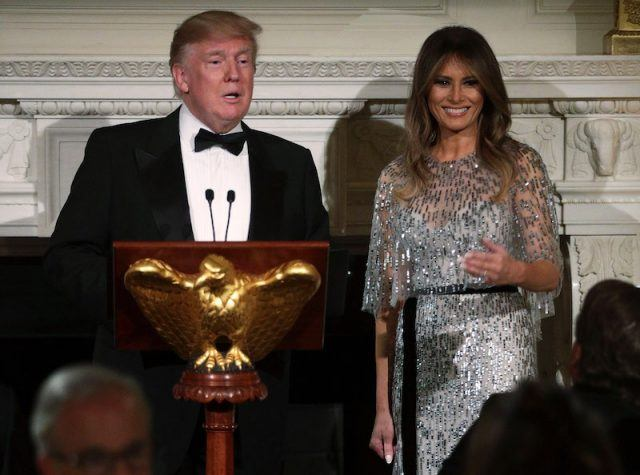 President Donald Trump standing at a podium with Melania trump.