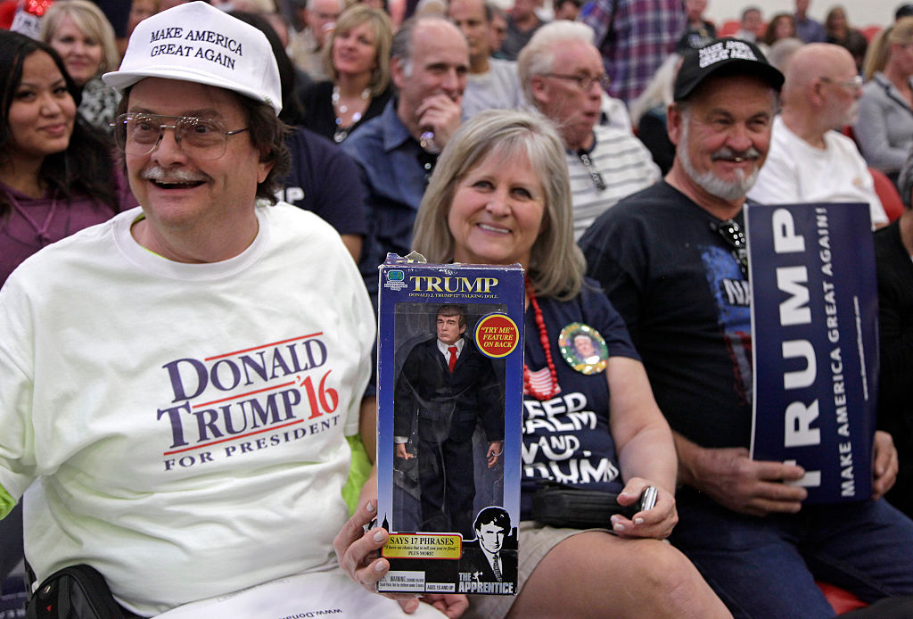 """Dave Queen and Cindy McLaughlin hold a Trump speaking """"The Apprentice"""" doll during a rally at the South Point Hotel in Las Vegas, Nevada"""