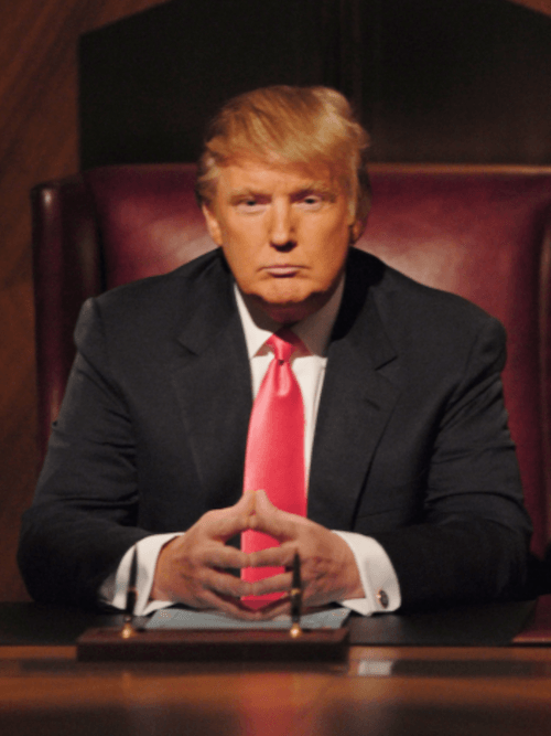 Donald Trump sitting at a desk on 'The Apprentice'.