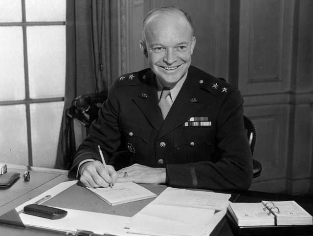 Dwight D. Eisenhower signing documents on his desk.