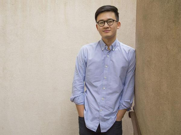 Eddie Huai smiling and leaning against a wall.