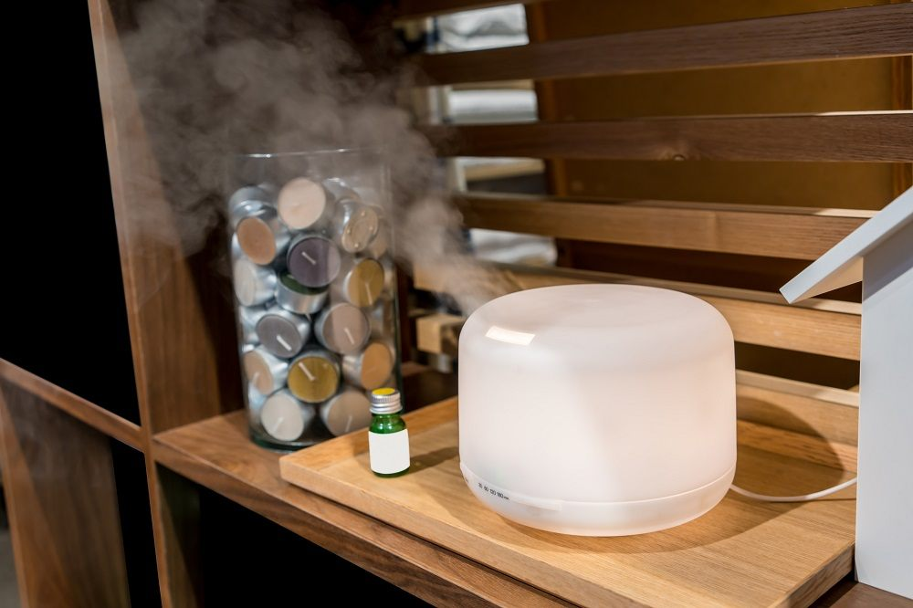 Electric aroma oil diffuser on wooden floor