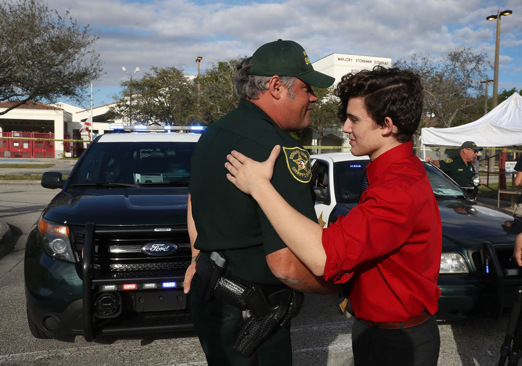 Alfonso Calderon a Junior at Marjory Stoneman Douglas High School speaks with Broward County Sheriff officer Brad Griesinger as he guards the front gate of the school.