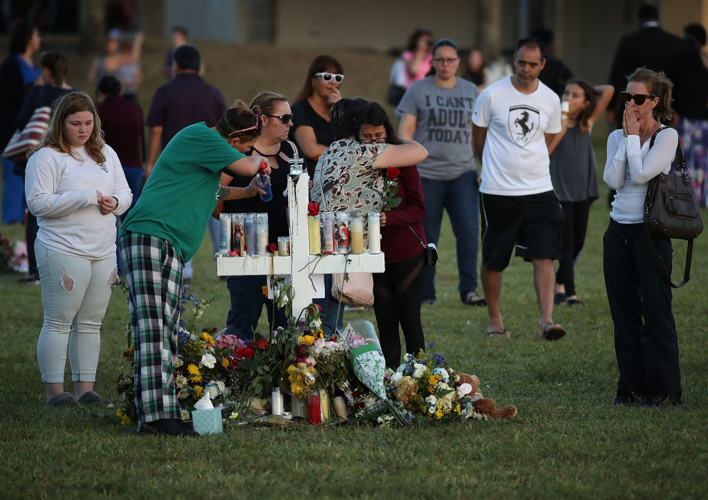 People visit a memorial at Pine Trails Park on February 17, 2018 in Parkland, Florida