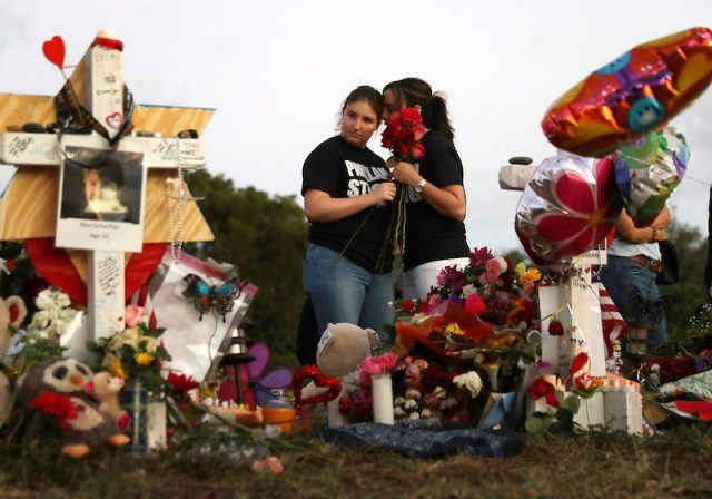 A pair of student mourners standing in front of several memorials.