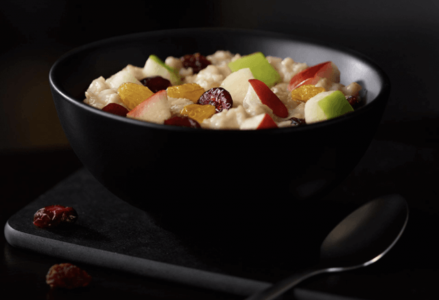 Oatmeal and fruit in a black bowl.