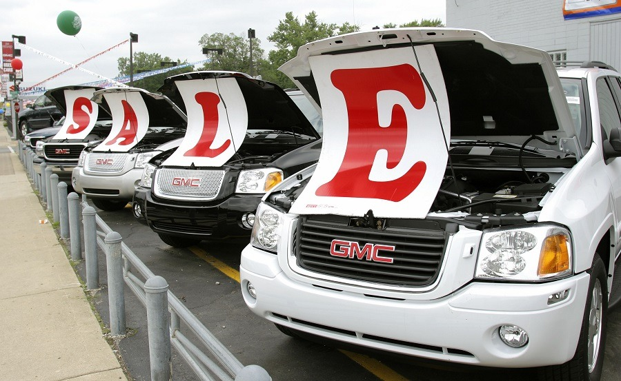 Sale signs lie on vehicles at a General Motors Chevrolet dealership