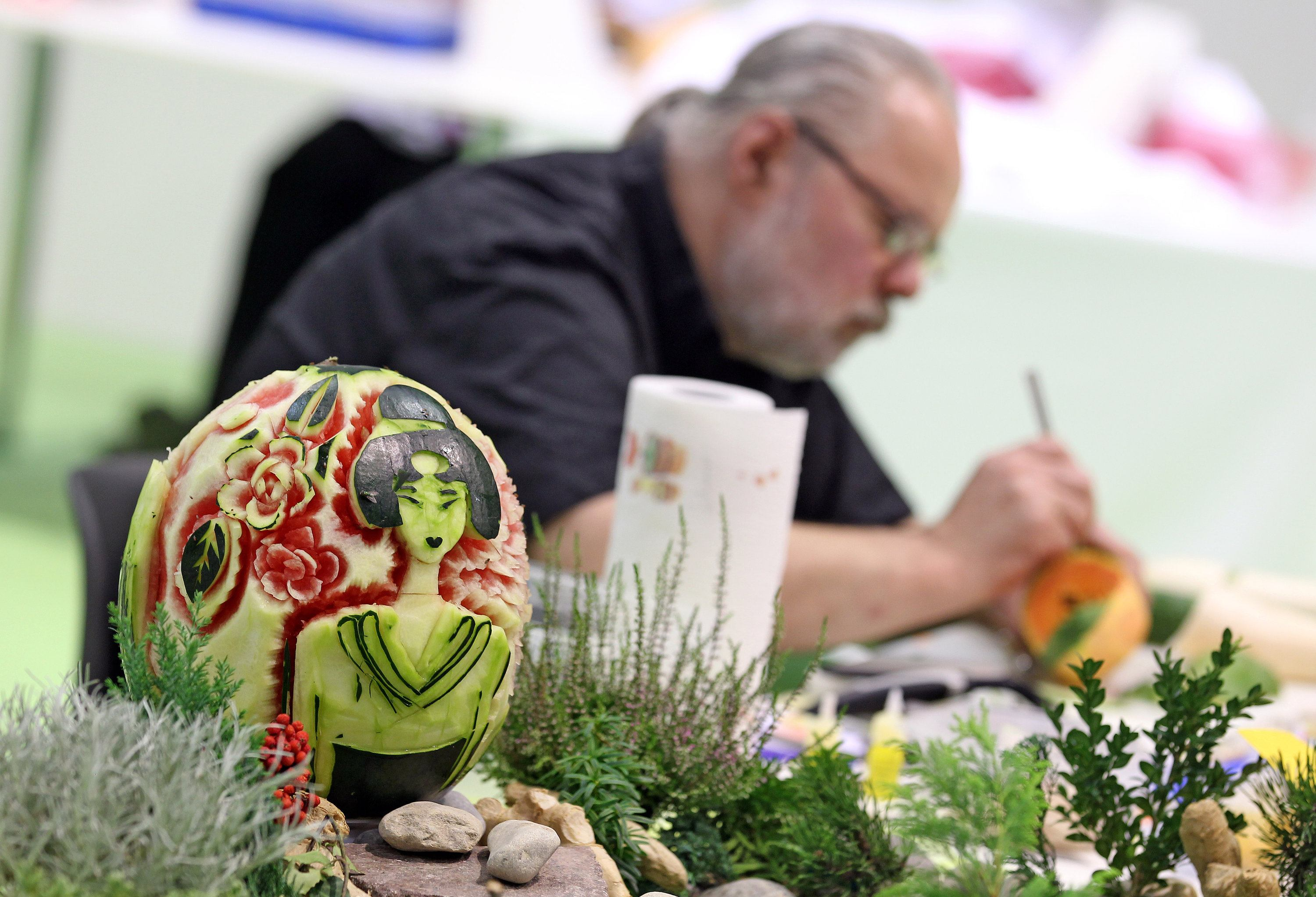 a german artist demonstrates fruit carving with a melon