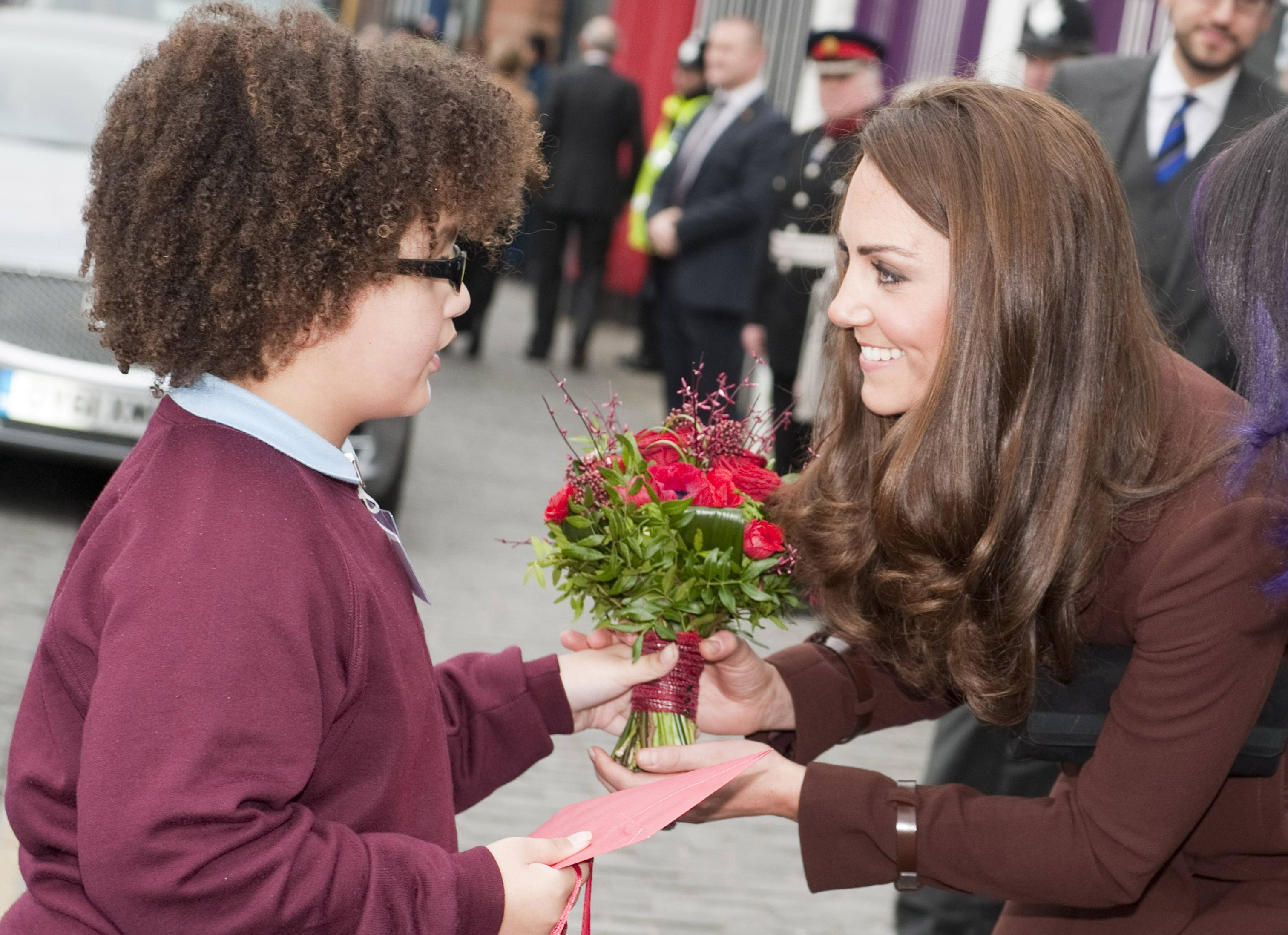 Eight-year-old Jaqson Johnston-Lynch presents Catherine, Duchess of Cambridge a posey of red roses and Valentine's Day present.