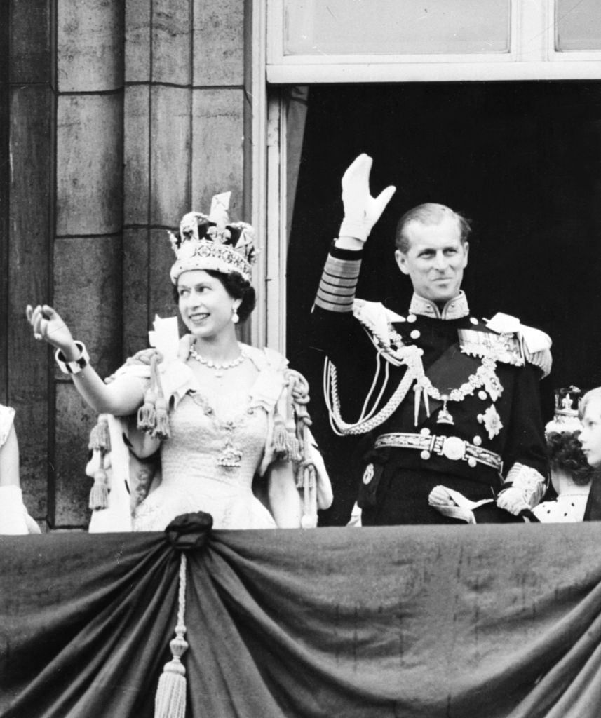 Queen Elizabeth II accompanied by Prince Philip waves to the crowd, 02 June 1953 after being crowned solemnly at Westminter Abbey in London.