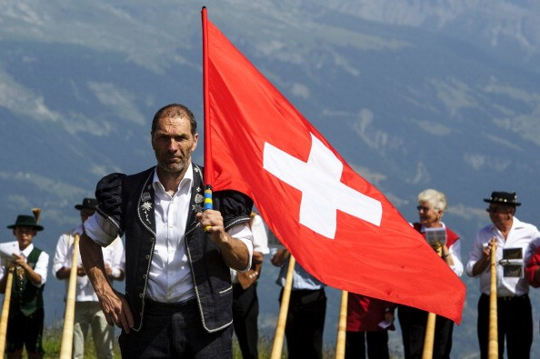 A flag thrower looks on as alphorn players prepare to perform in Nendaz, Switzerland.