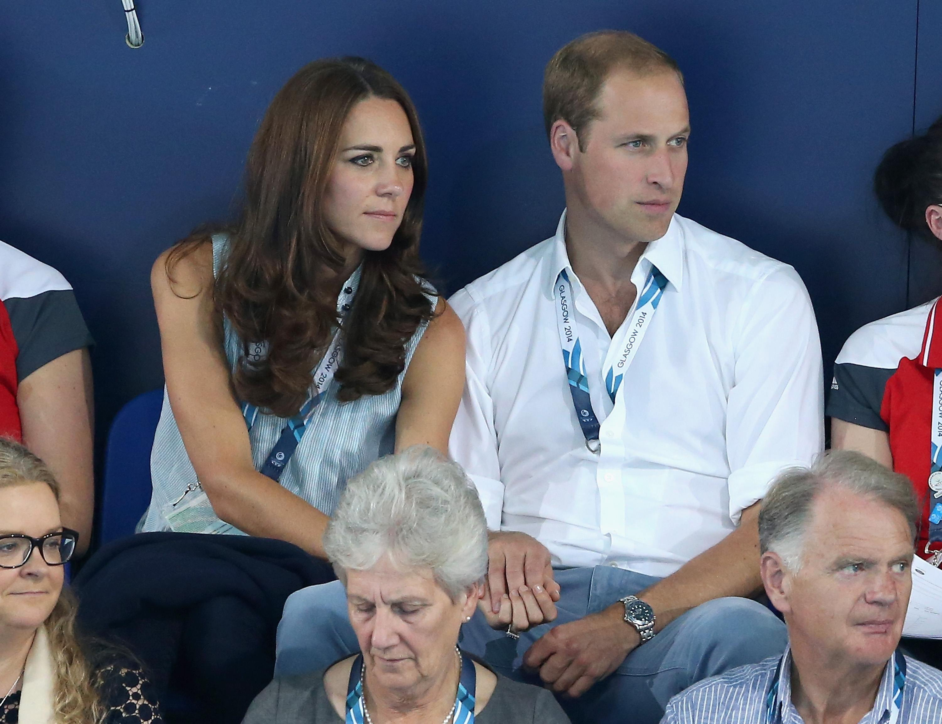 Catherine, Duchess of Cambridge and Prince William, Duke of Cambridge hold hands as they watch the swimming at Tollcross Swimming Centre during the 20th Commonwealth games on July 28, 2014 in Glasgow, Scotland.