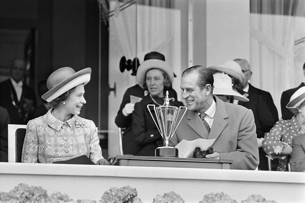 Britain's Queen Elizabeth II (2nd L) and her husband Prince Philip (2nd R), Duke of Edinburgh, share a smile in May 1972 as they attend a horse race at Longchamp racecourse, outside Paris during their five-day official visit in France.