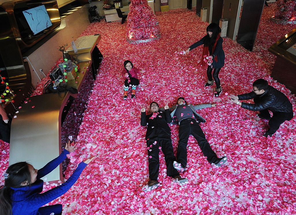 Single men and women toss peach petals to pray good luck for life and love on February 9, 2015 in Wuhan, Hubei province of China. A hall at the first floor of Wuhan's K11 Gourmet Tower scatterred peach petals to welcome the upcoming Valentine's Day which drew single men and women's interest.