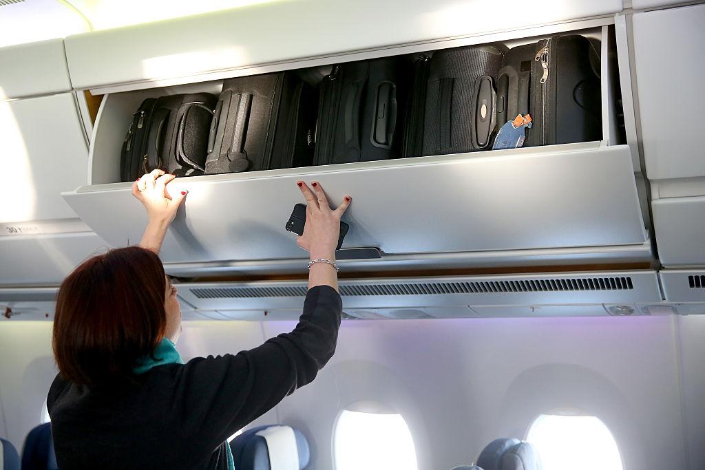 putting bags in overhead bin