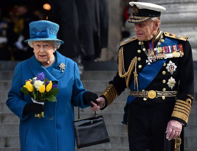 Queen Elizabeth and Prince Philip hold hands as they walk down steps.
