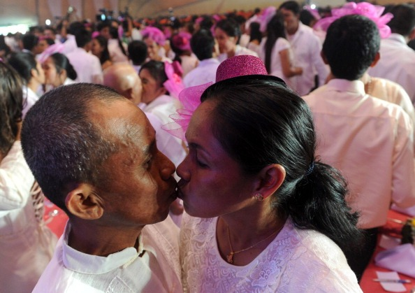 two people kiss during a mass wedding in the philippines