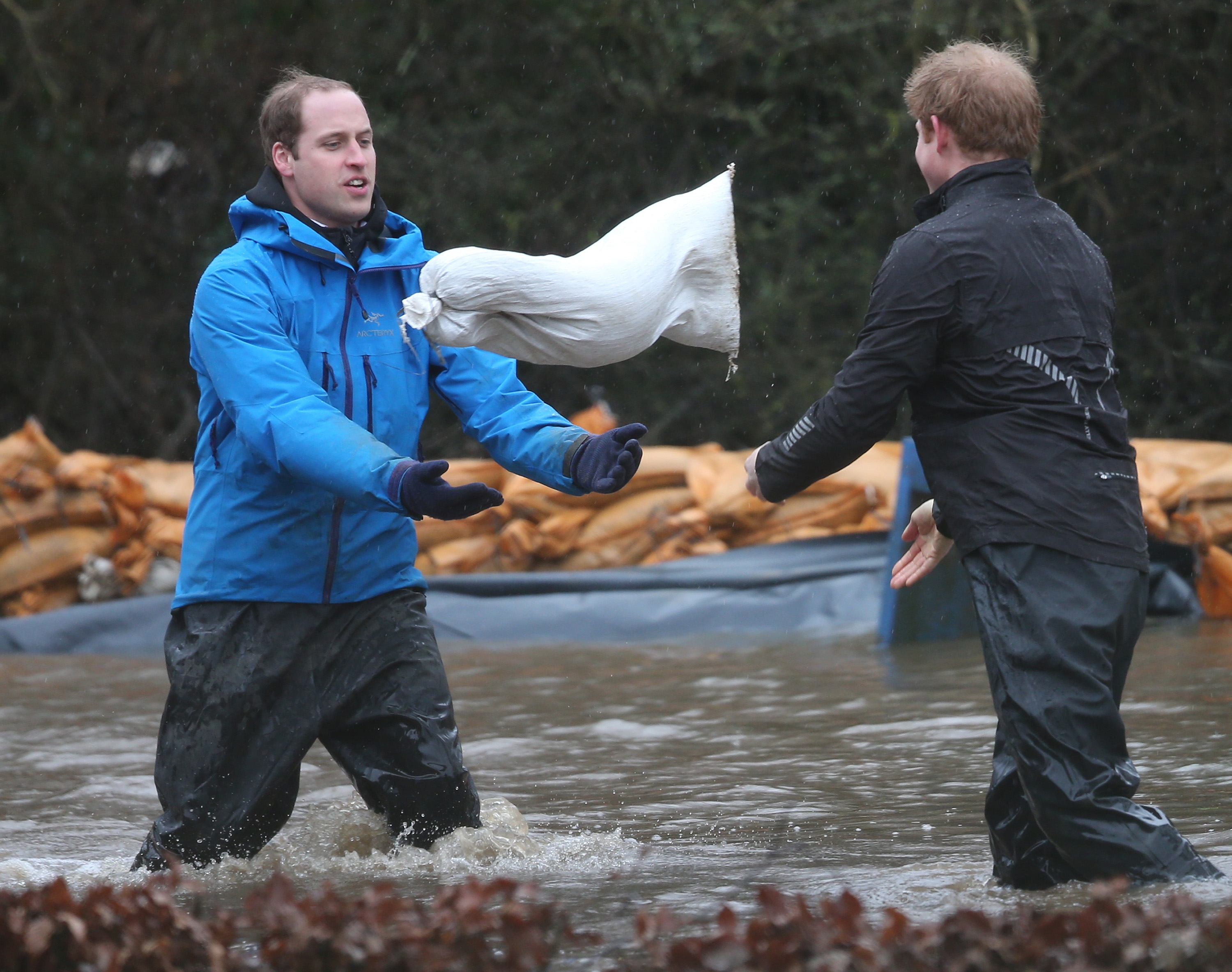 Prince William, Duke of Cambridge (L) catches a sandbag thrown by his brother Prince Harry as they build a flood wall