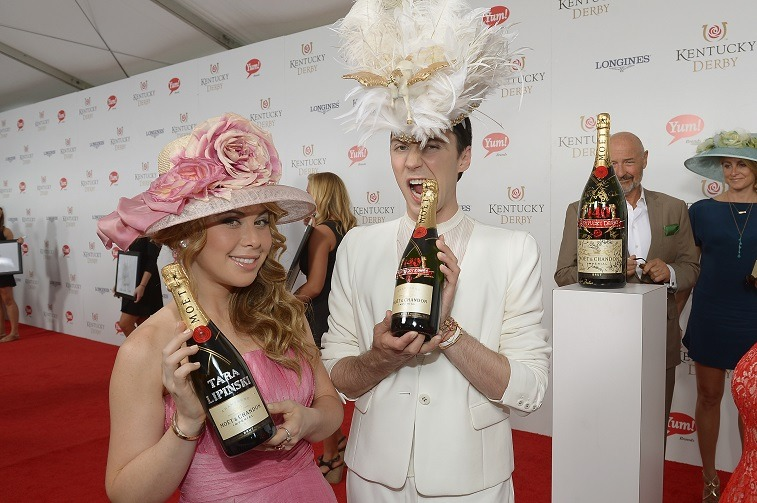 Figure skaters Tara Lipinski (L) and Johnny Weir toast with Moet & Chandon at the 140th Kentucky Derby at Churchill Downs on May 3, 2014 in Louisville, Kentucky.