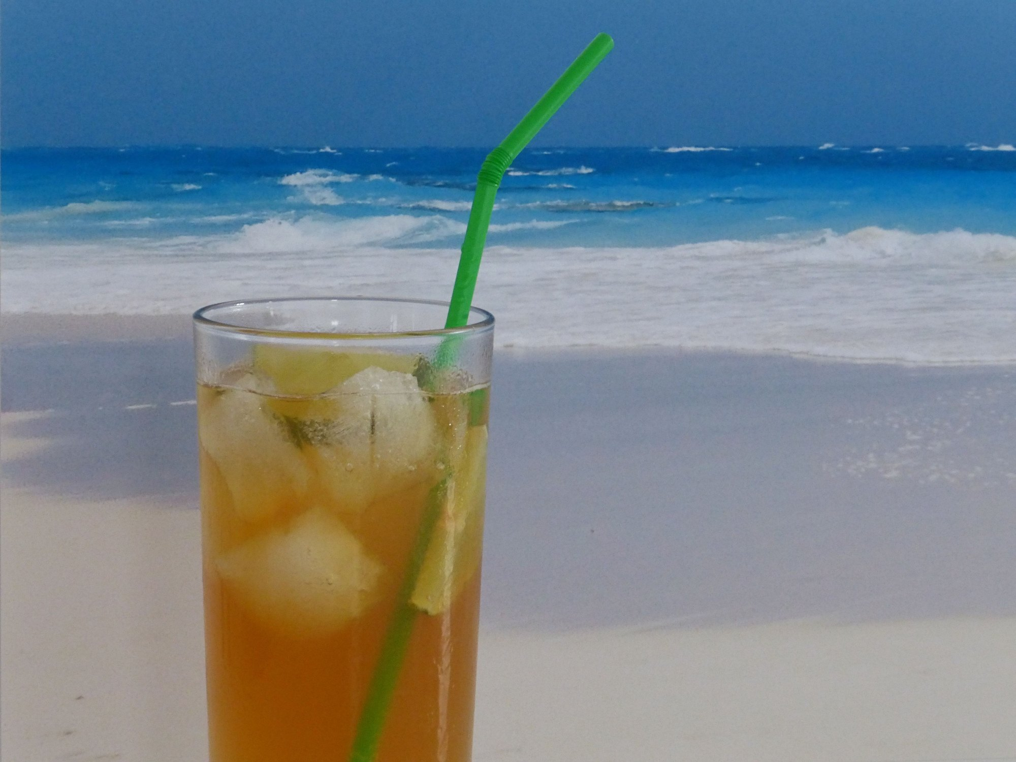 dark n stormy cocktail in front of a beach