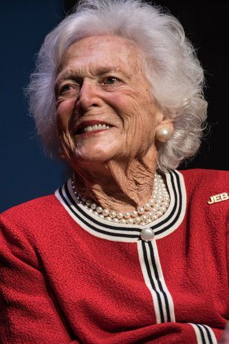 Barbara Bush smiling in a red suit and pearls.