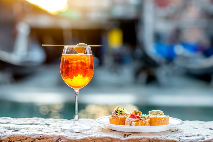 Spritz Aperol drink with venetian traditional snacks cicchetti on the water chanal background in Venice. Traditional italian aperitif.