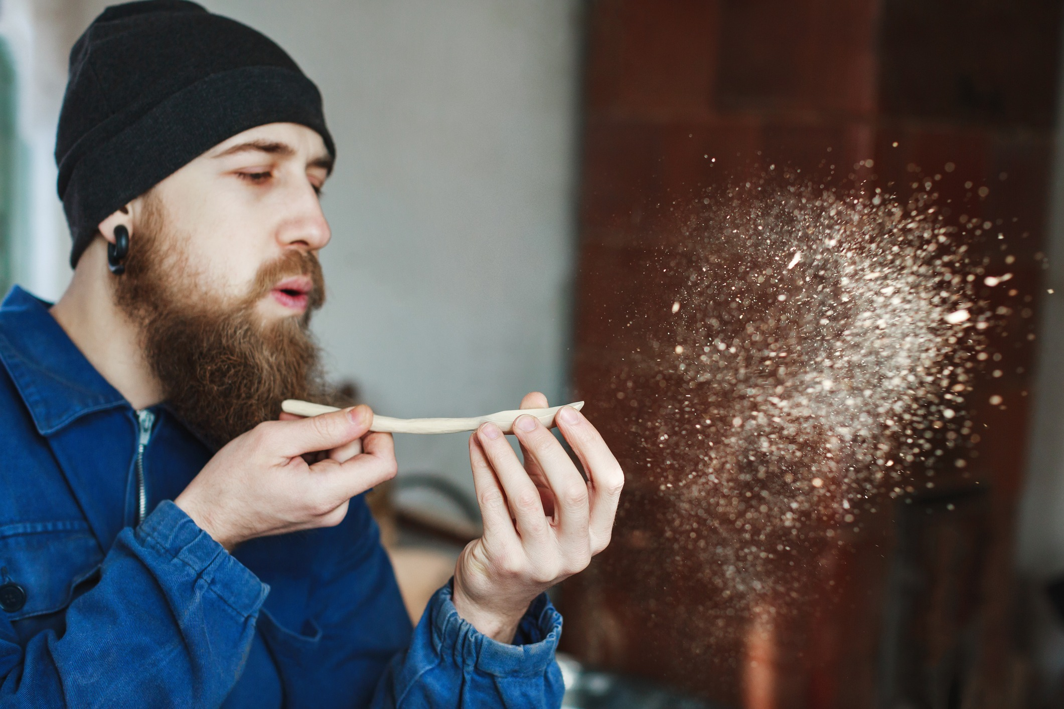 Man with a beard wearing blue jeans suit and black hat holding wooden spoon and blowing dust